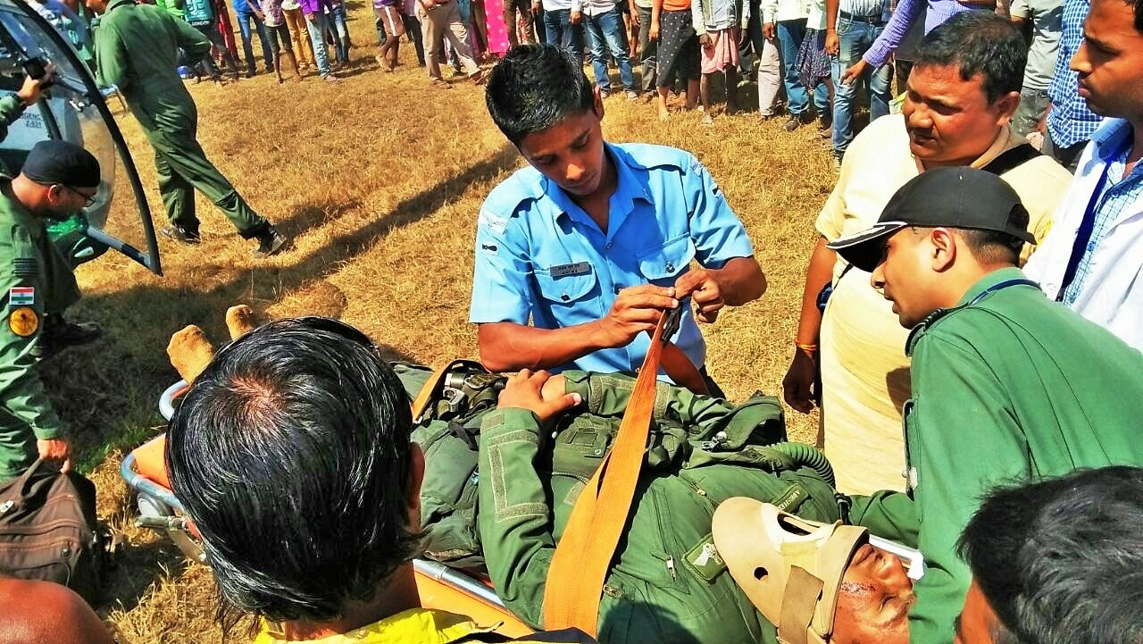 <p>IAF emergency crew members tending to the injured pilot after his aircraft crash-landed on the riverbed of Swarnarekaha river in Mahuldungri under Baharagora police station in East&#8230;