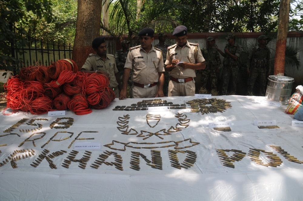 <p>Police officials inspecting arms and&nbsp;ammunition recovered from CPI Maoists during a press conference in Ranchi&nbsp;on Sunday.</p>