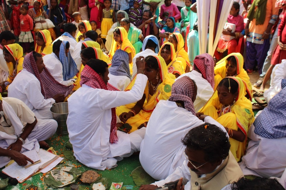 <p>Brides and grooms perform rituals during a mass marriage at JAP ground in Ranchi on Saturday. Around 51 poor tribal couples took part in the mass marriage ceremony.&nbsp;</p>