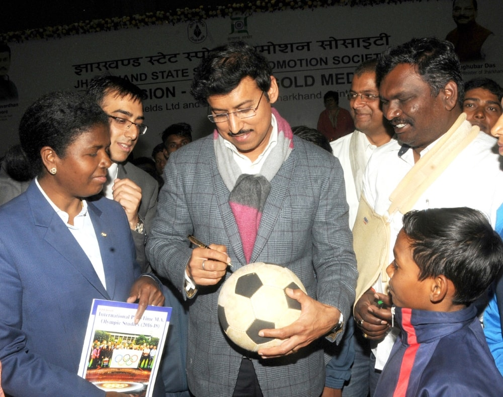 <p>Union Minister of youth Affairs and Sports Rajyavardhan Singh Rathore gives his autograph on a football to a boy during the sports programme on ''Our Mission-Olympic Gold…