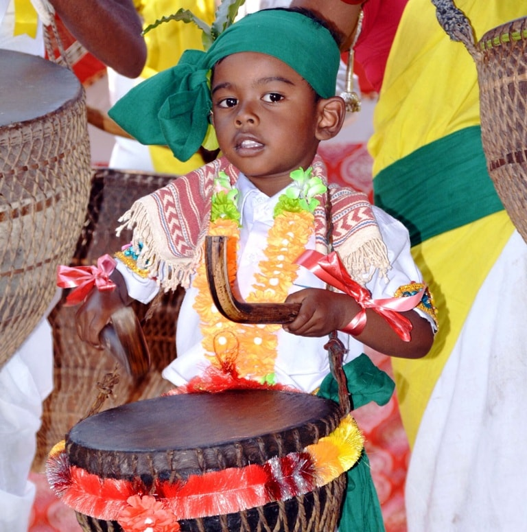 <p>A kid dressed in traditional attire seen beating 'mandar' - a traditional musical drum during the Sarhul festival celebrations in Ranchi on Tuesday.</p>