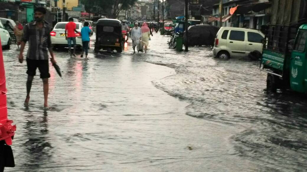 <p>Due to lack of plain drains,rain water flooded roads near Kadru overbridge railway line and entered into houses of residents there.</p>