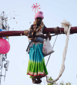 <p>People watch acrobatics being performed by a devotee during the Manda festival in Ranchi on Friday.</p>
