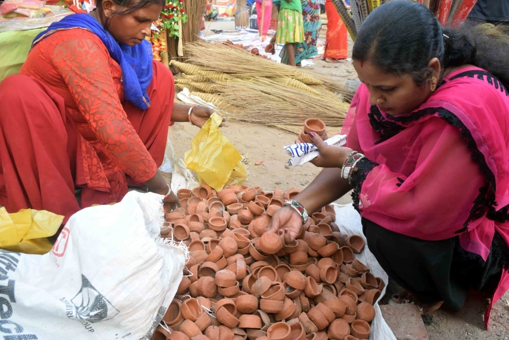 <p>Traditional earthen Diwali diyas are still a favorite of the womenfolk.A women busy purchasing diyas from a road side stall in Ranchi on Wednesday.</p>