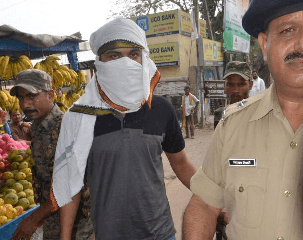 <p>Cop together with a face covered man.This man called Aman,a shooter,who was nabbed and arrested by the police in Mirzapur,was sent to jail in Dhanbad.&nbsp;</p>