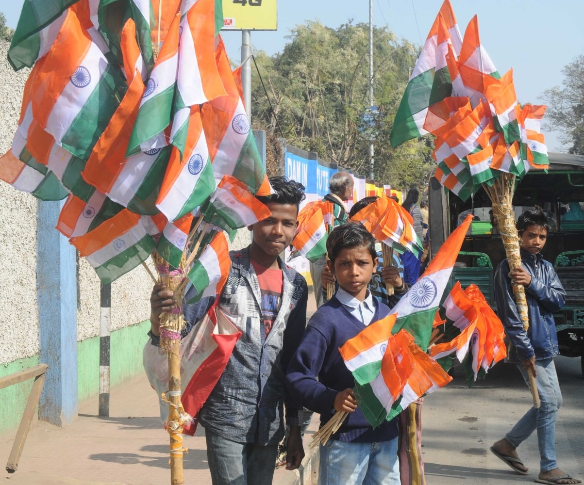 <p>Boys selling the Indian National Flags on roadside on the eve of Republic Day, in Ranchi on Thursday.&nbsp;</p>