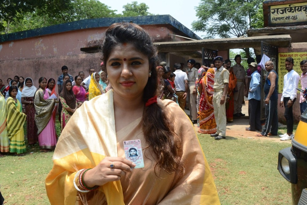 <p>Neha Mahto wife of former Jharkhand Deputy Chief Minister and AJSU Party Chief Sudesh Mahato, show her Election Commission cards as she stands in a queue to cast her vote for Silli…