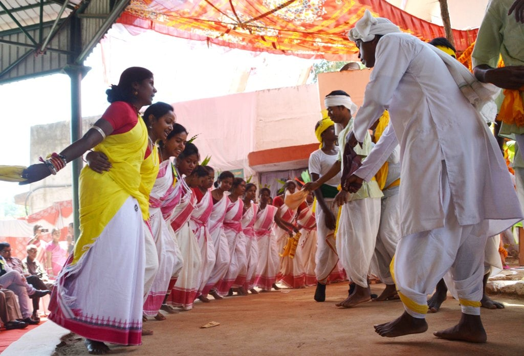 <p>Men & Women folks perform a traditional dance at an 'akhara' during the Sarhul festival in Ranchi on Tuesday.</p>