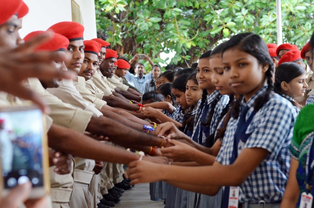 <p>School girls tie Rakhi on the wrists of Police jawans as they celebrate Raksha Bandhan at an event at New Police line in Ranchi on Saturday.</p>