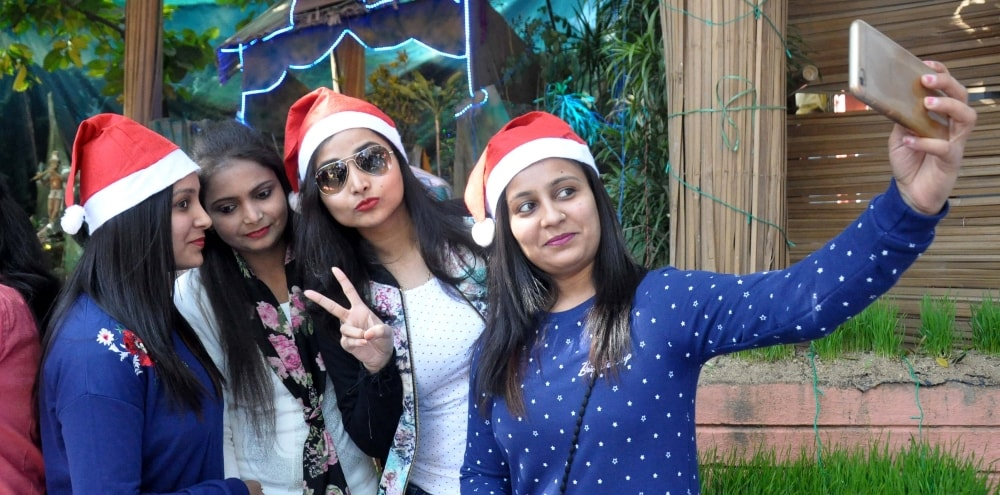 <p>Girls taking a selfie outside Mahagirija Ghar as they celebrate Christmas festival in Ranchi on Monday. </p>
