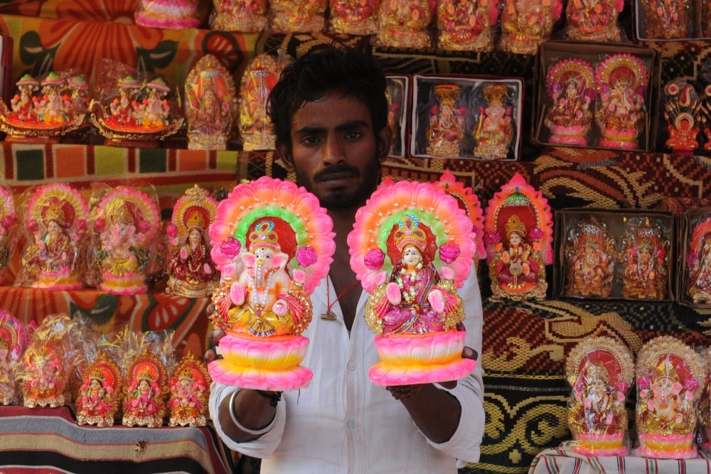 <p>A man buys idols of goddess Laxmi and lord Ganesha from roadside stalls on the eve of Hindu festival Diwali on October 17, 2017 in Ranchi, Jharkhand.  Diwali also known as…