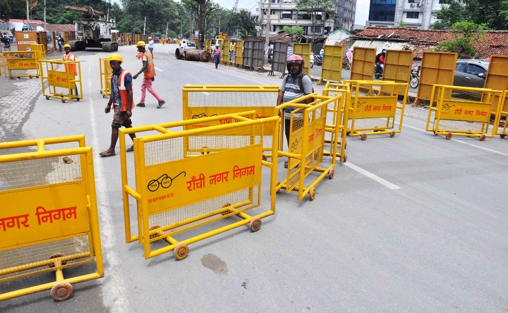 <p>Vehicles move on a diverted route during the ongoing Kantatoli flyover construction work in Ranchi on Monday.</p>