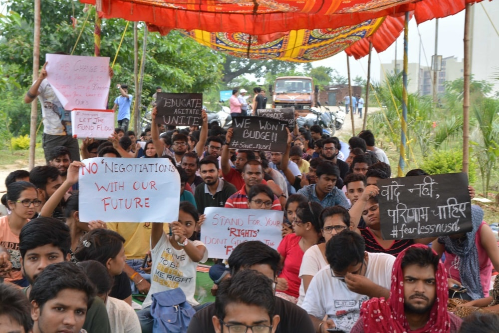 <p>Students of the National University for Study and Research in Law (NUSRL) staging dharna ageist their vice Chancellor (VC) in-charge Gautam Chaudhary after locked down the main…