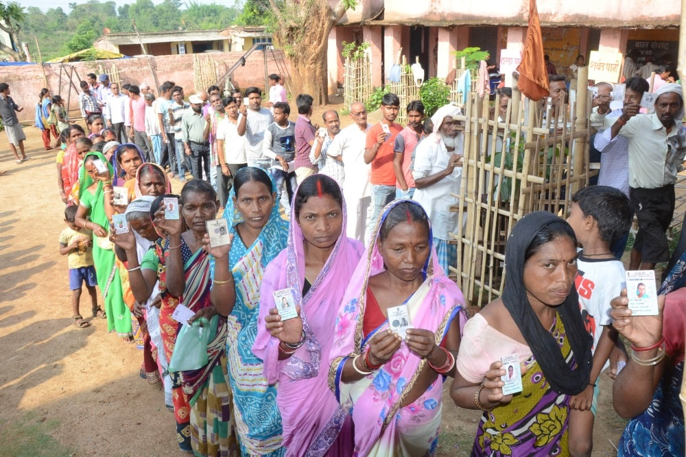 <p>Voters show their Election Commission cards as they stand in a queue to cast their vote for Silli Assembly bypoll at a polling station in Silli 63 KMs from Ranchi on Monday. </p>…