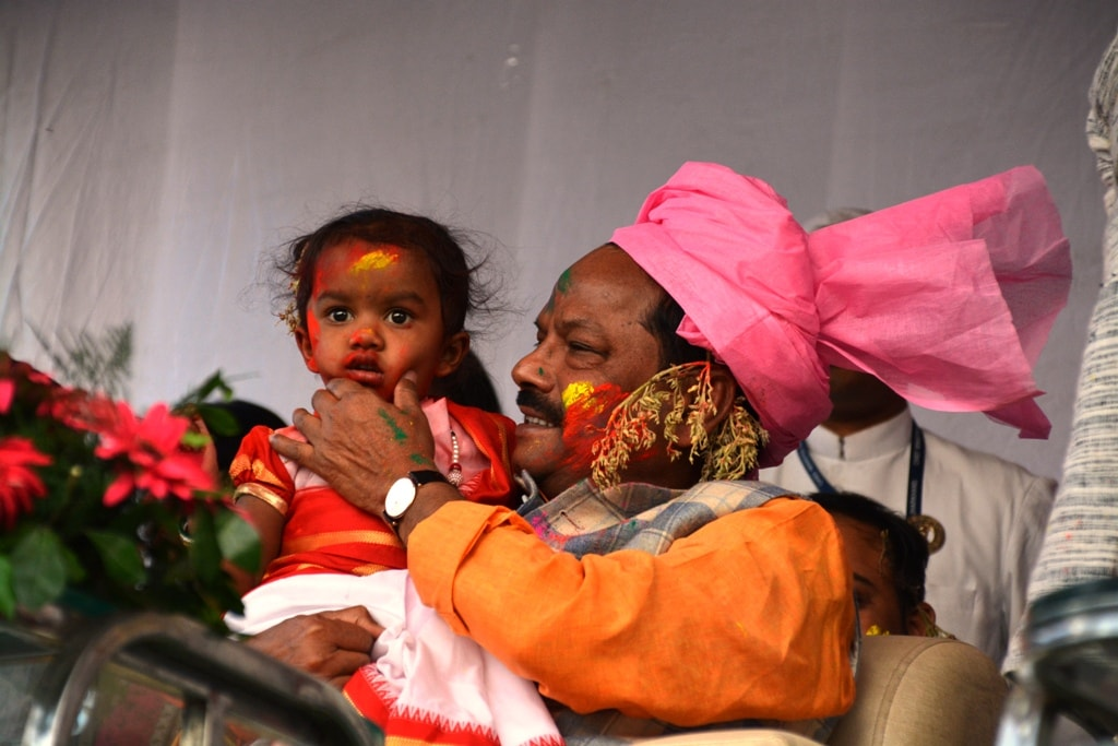 <p>Jharkhand CM Raghubar Das holding a baby girl in his lap while participating in Sarhul festival in Ranchi on Tuesday.</p>
