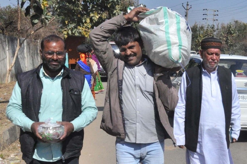 <p>RJD workers carry Chuda-Dahi (flattened rice and curd) for party Chief and former Bihar Chief Minister Lalu Prasad Yadav for Makar Sankranti outside Birsa Munda Central…