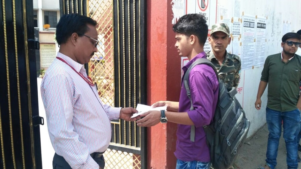 <p>An invigilator inspecting the admit card of a NDA aspirant at a.city based school in Ranchi.</p>