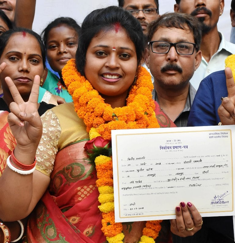<p>Newly elected unopposed from ward no-19, Roshni Khalkho showing victory sign and certificate at Collectorate in Ranchi on Tuesday. </p>