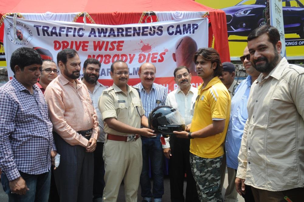 <p>City SP Ranchi Aman Kumar distributes helmet to a motorcyclist during a Traffic awareness camp organised by Punjabi-HinduViradari Yuva Munch at Sujata Chowk in Ranchi on Friday.…
