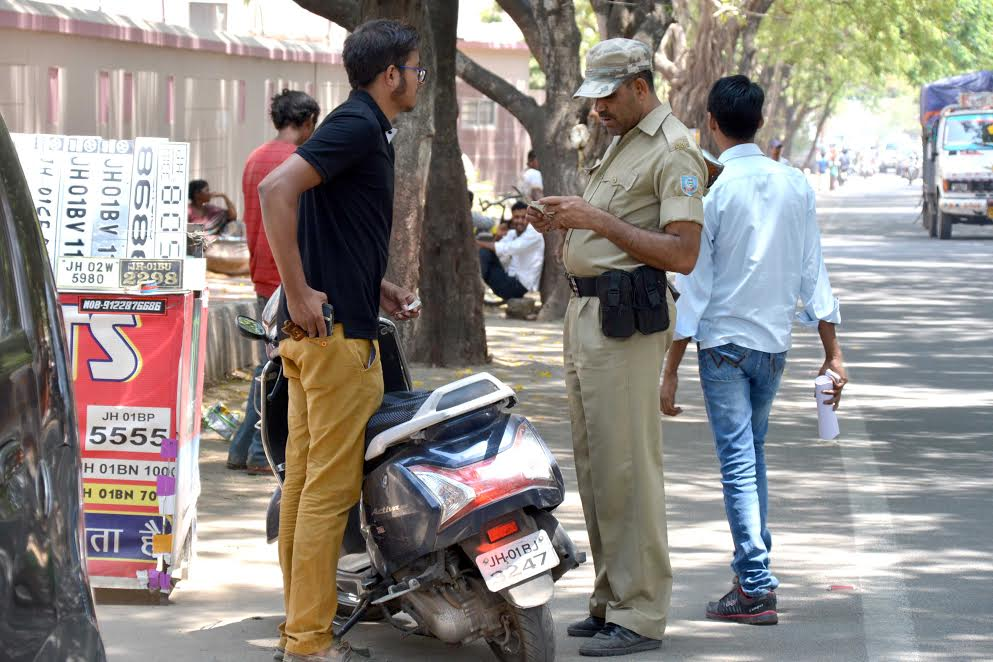 <p>Police personnel check documents of a two-wheeler rider who violate the rules during a special Helmet Checking Drive launched by the state police at Harmu road in Ranchi…