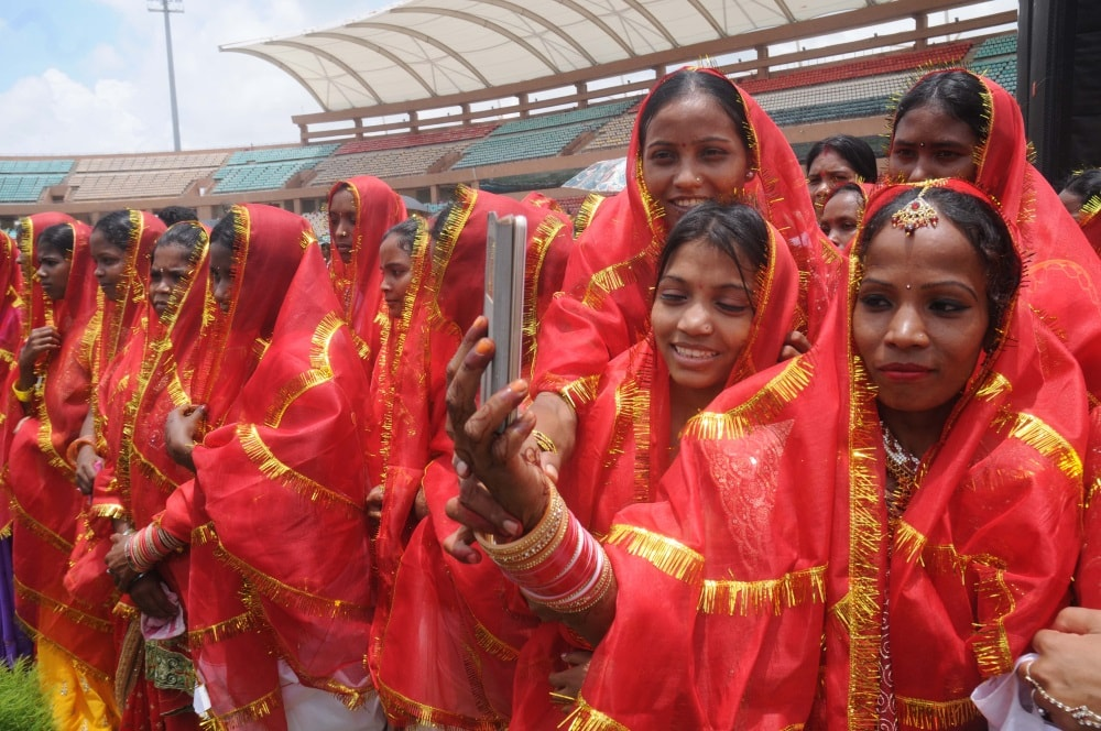 <p>Newly marriage tribal brides takes selfie during a mass marriage organised by Central Sarna Committee at Mega Sports complex Hotwar in Ranchi on Thursday.</p>