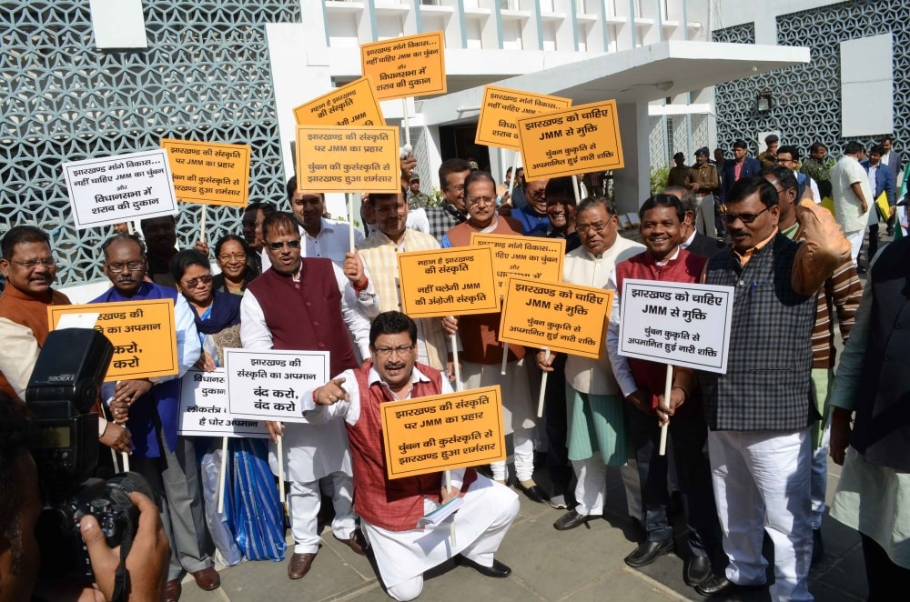 <p>BJP legislators holds placards shouting slogans against the 'Kissing Competition' organised by Littipara legislator Simon Marandi outside Jharkhand assembly during ongoing…
