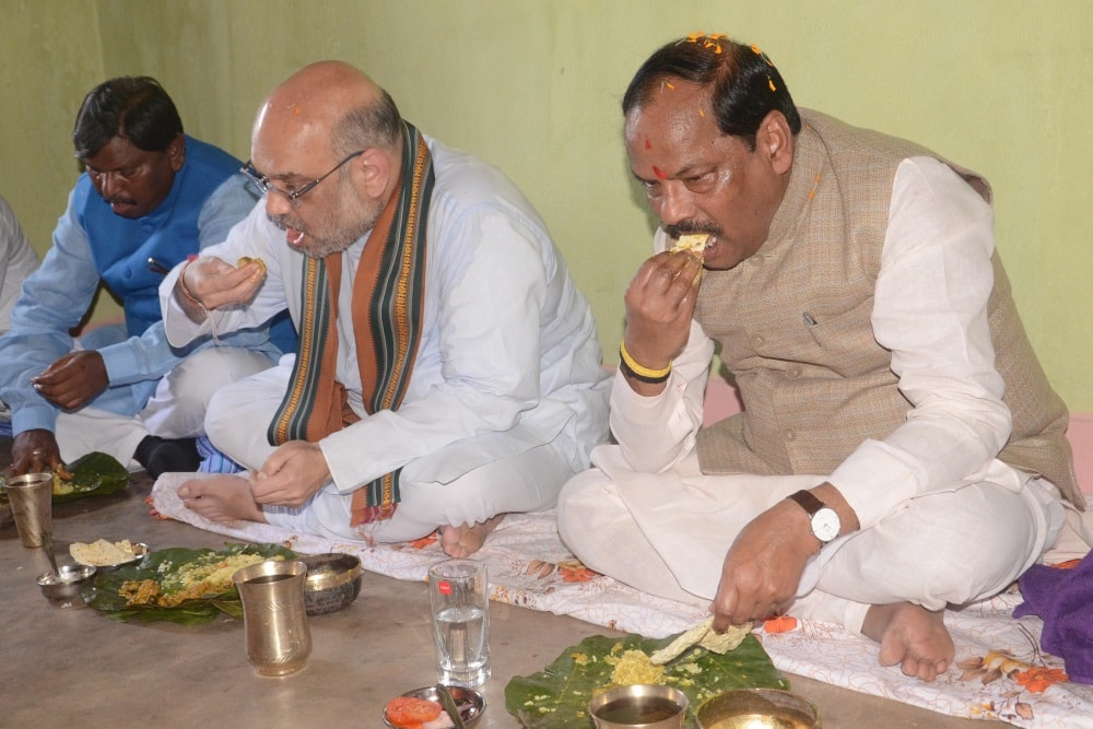 <p>BJP National President Amit Shah along with Jharkhand Chief Minister Raghubar Das (R) and former Jharkhand Chief Minister Arjun Munda takes lunch at a tribal BJP worker's house…