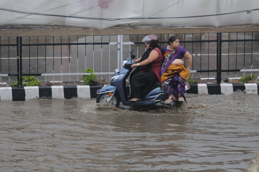 <p>Ranchi, Jharkhand 8 June 2018: People wade through on a messy water flooded road after heavy rains in Ranchi on Friday.</p>