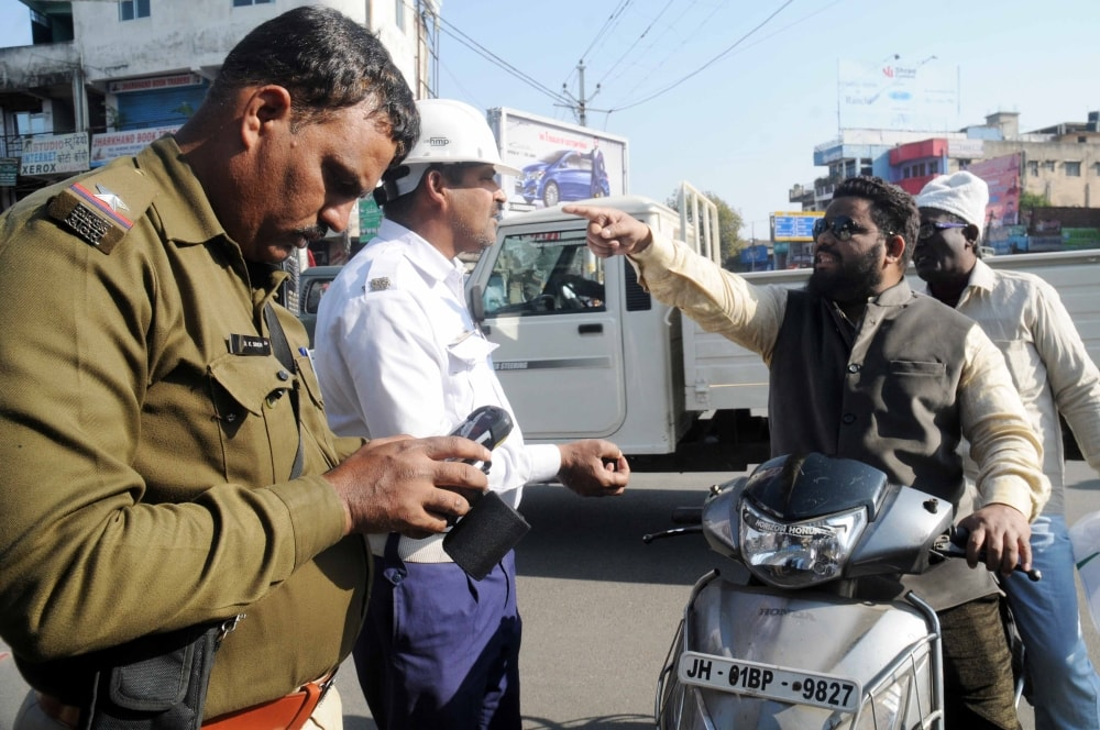 <p>Atraffic officer D K Singh issuing an E-challan for violating traffic rules to a scooty rider at Kantatoli Chowk in Ranchi on Thursday.</p>
