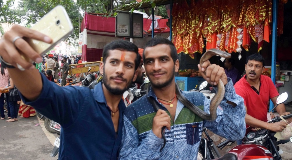 <p>Two youngsters takes selfie with a snake at Pahari Mandir on the occasion of Nagpanchami festival in Ranchi on Friday.</p>