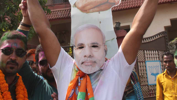 <p>BJP worker wearing the mask of Prime Minister Narendra Modi celebrate the party's victory in the assembly elections, at party headquarter in Ranchi on Saturday.</p>