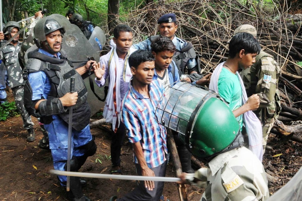 <p>Security personnel detain villagers while carrying out a search operation at the remote village Ghagra, where MP Karia Munda's three bodyguards, belonging to Jharkhand…
